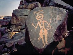 Tageuit, Air Teneré, Niger. Several figures have a hand drum, basket, or calabash looped over their arms. Rock art