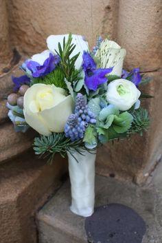 he beautiful Bridesmaid's posy of Muscari, Classic Blue Hydrangeas, Blue Spruce, Avalanche Roses, Ranunculas, Delphinium, Rosemary, Champagne Grass, Eryngium and Albiflora Brunia