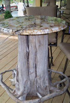 Tree trunk bar table with granite top. Notice the foot rest.  My hubby made it!