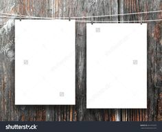 Close-up of two blank frames hanged by pegs against dark wooden background
