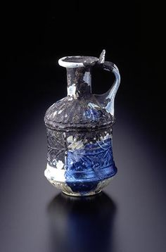 https://flic.kr/p/854ci8 | Roman Mold-Blown Glass Bottle with Plant Design | Mold-blown glass, 1st century C.E.  This bottle was blown from bluish semi-transparent glass and then formed in a 3-part mold. Its base was formed from a separate mold. The mouth rises vertically and a handle stretches from shoulder to mouth. The shoulder and hips of the bottle are decorated with a relief pattern of chrysanthemum-like flowers, with right-left symmetrically arranged branches set in relief on the…