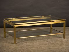 Pierre Vandel Gilded Brass Coffee Table, Two Level with Glass, France c.1975. The architectural appearance of this table with the top frame elevated by rectangular supports is quite striking and gives the table its superb modern presence. The modern lines of this table work well with both a Minimalist aesthetic as well as a more traditional interior.