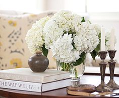Design Solution - Tablescapes as the finishing touch to a beautiful room. Nothing completes a room like fresh flowers.    The repetitive use of white, neutrals and varying heights of simple objects in this tablescape make it a lovely sight. #bhg.com
