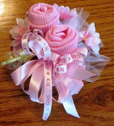 Baby shower corsages handcrafted to match your color choices. Each corsage is made using a pair of infant socks, flowers, miniature baby rattle, net, pearls, pink or blue dipper pins or miniature pacifier and ribbon. The choices listed are available or custom order can be made. Just select
