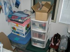The apple box is full of yarn. Fabric on top needs folded and put away. Tool bag, distilled water, and #2 sewing machine. Box  full cut up blue jeans, below that is finished quilts. The bins are full of thread and scraps of fabric. Samples pinned to the wall. Empty boxes waiting to be made into magazine rack and covered. Small ironing board to left. I would like to somehow display some of the quilts I have made, and also the quilt my grandmother made for my dad when she was in her 80's.