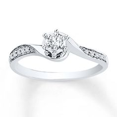 A diamond is swept with waves of gleaming sterling silver decorated with more diamonds in this elegant promise ring for her. The ring has a total diamond weight of 1/6 carat. Diamond Total Carat Weight may range from .145 - .17 carats.