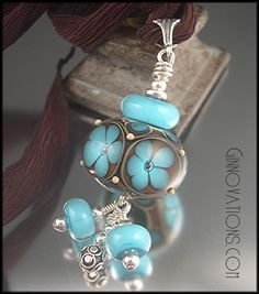 """The focalpoint of this pendant is an oversized round bead created with dark turquoise, two shades of transparent topaz, crystal clear, and just a bit of khaki beige. The focal is decorated with 5 """"windows"""", each featuring an encased flower with a big bubble cente"""