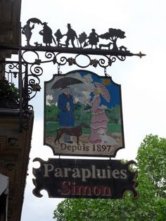 """Paris - what a fantastic hanging sign for """"Parapluies Simon"""", an umbrella shop. Love the detail of the wrought iron figures along the top. Can be found at 56 Boulevard Saint-Michel. Umbrella Shop, Storefront Signs, Old Pub, Pub Signs, Shop Fronts, France, Store Signs, Tour Eiffel, Hanging Signs"""