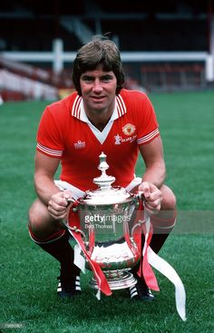 Sport Football Manchester United's Martin Buchan holds the FA Cup trophy which they won by beating...