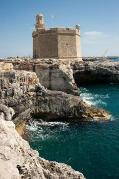 Antigua fortaleza de la torre en las rocas del mar contra el cielo azul, Ciutadella de Menorca, Menorca, España