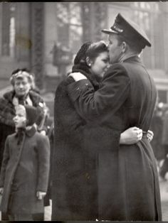 Soldier tenderly kisses his girlfriend's forehead as she embraces him.