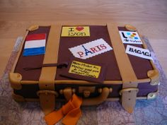 Leather suitcase - A suitcase for my father-in-law Michel who travel all around the world! This is a chocolate cake with chocolate ganache and custard filling covered with fondant. All the details are fondant. The stickers are all hand painted. I put some gold luster dust on the metal parts to give a real effect. The map cardboard I made is on the travel theme. Really fun to make cake!