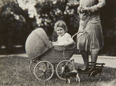 Royal carriage: Queen Elizabeth II, when she was aged two, holds on tight to the rope of her toy horse in a photograph taken by her father, then Duke of York