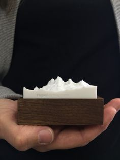 Our topographic models are of existing mountain peaks or ranges. Both the height of the wood base and mountains are to scale with the bottom of the base representing sea level. The wood base can also function as a box and has a wool felt interior. The mountains are created using 3D printing technology. A North arrow is also indicated on each model. We can create almost any peak in a variety of colors. A great gift to remember that epic climb or trip