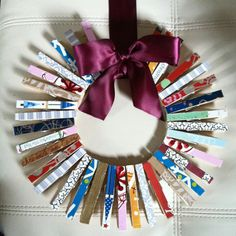 DIY Holiday Wreath: wooden clothes pins, scraps of wrapping paper or scrapbook paper, mod podge, ribbon, and a cardboard circle. Ta da! :)