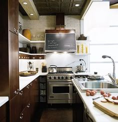 Kitchen with walnut cabinetry, white quartz counters and chalkboard decal on stove vent hood.
