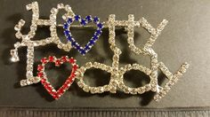 """Cheer on the Ole Miss Rebels wearing one of these Hotty Toddy Rhinestone Pins. Rhinestones are clear with a red & black heart in a silver tone setting. Pins are 3"""" wide x 2 """" tall and have a pin back. Perfect for fundraising, for Sorority Sisters, for Loyal Fans. Pins are new in cellophane. Ships from Illinois. 26 pins are available for purchase. Email tammy@blessingsandbling.com for purchase info."""
