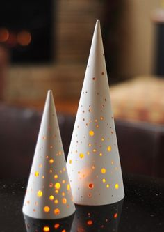 DIY modern perforated christmas trees...uses simple paper mache cones found at the craft store...drill a few holes (sand them a bit as needed) and spray paint white.  Set a LED tealight (battery operated) under the cone for the lit up effect!    Looks just like those expensive ceramic ones I saw somewhere but CHEAPER!  :)