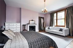 purple. pale purple/lavender bedroom with white furnishings and grey and silver fabrics. white and black fireplace, old antique leaning mirror. traditional architecture mixed with modern furnishings and antique accessories. mid-1800s Victorian townhouse London.
