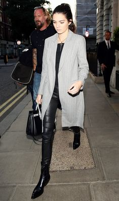Kendall Jenner wears a black top, cross necklace, pinstripe coat, leather leggings, ankle boots, and a Saint Laurent tote bag