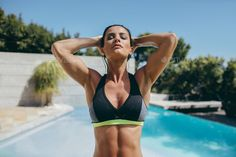 Fit young woman in sports bra at poolside by jacoblund. Outdoor shot of fit young woman in sports bra standing at the poolside with her hands behind head and eyes closed. Fe...