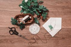 Threads, pins, needles, scissors lying on wooden background. White envelope and a white rose. Greeting card. Conceptual photography. Wedding invitation card. Valentine day. Flat lay, copyspace