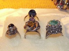 Here are 4 different genuine silver and gem stone rings i hand crafted myself.The top one is a genuine black onyx that i placed in a gold plated sterling silver ring.It is a size 6. $50.The second one is a genuine cabochon black onyx set in a vintage style sterling silver setting ,size 7. The 3rd in the middle is a sterling silver rose with a genuine natural purple amethyst and a natural citrine gem stone. This all sits on a sterling silver band that is a size 7 or 8 i am not sure. $55.