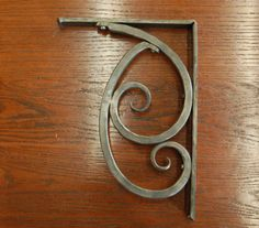 If I had to have curls then this is pretty cool! Iron Shelf Bracket - Hand Forged by a Blacksmith - 9.5 x 12 Inch - Style 05. $43.00, via Etsy.
