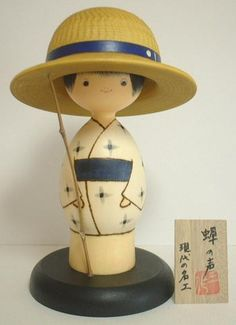 Semi Boy by Sansaku sekiguchi. This is a boy on a summer day. His straw hat is shown through the technology of carving