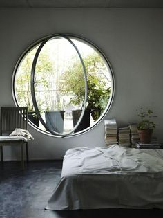 A large modern porthole window pivots on axis; photo by Debi Treloar for The Natural Home by Hans Blomquist. Remodelista