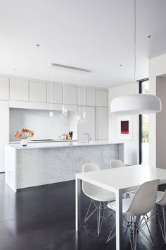 Ultra modern kitchen with white high gloss handleless cabinets with a marble island, white mdf kitchen table and white Eames Eiffel chairs.