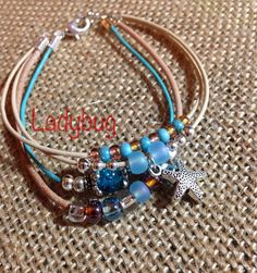 Bracelet – Multistrand leather cord, glass beads, metal starfish charm, lobster clasp, nickel/lead free