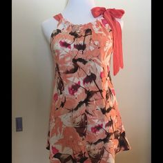 Banana Republic Soft Coral Sleeveless Top This is a 100% silk coral color top.  Gathered at the neck.  Ties at the shoulder.  Beautiful over summer white pants!  Measures 21 in. armhole to armhole; 23 1/2 in. width at hem; 18 in. length armhole to hem. Banana Republic Tops