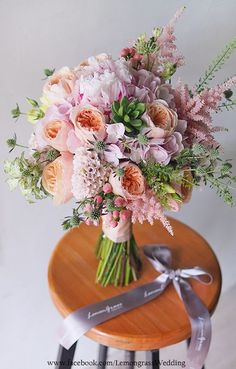 Romantic bridal bouquet with soft pink, orange and greenery