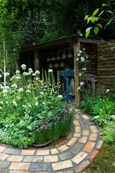 Harpur Garden Images Ltd :: Silver Flora brick circular curved winding path bed border chives Allium Mont Blanc potters shed shack hut garden building shelter structure Design: Margaret Archibald, Val Donnelly, Rae McNab and Coralin Pearson fo