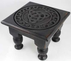 Hand carved of wood and antiqued to provide a dusky, aged appearance, this altar table is a wonderful display of craftsmanship and mysticism, with its display of the three points of a triquetra. Its four solid legs are beautifully crafted to lend stability upon most surfaces while creating the impression of a flowing mind. The table top extends out from this base to create a wide expanse for your altar tools and ritual crafts that is also richly imbued with carvings that form an intric…