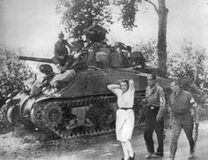 A French woman accused of being a German sympathizer being marched past an American Sherman medium tank, near Pre-en-Pail, Normandy, France, Aug-Sep 1944