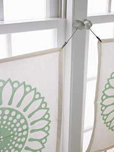 DIY Cafe Curtains. Hang square printed napkins from photo clips for an easy no-sew window treatment. The clips are hot-glued in place on the window moldings. If your windows are larger, stitch two napkins together.
