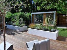 #Kleine #moderne #tuin in Londen met verhoogde hardhouten vlonder, witte bloembakken, kunstgras en buitenkantoor.: