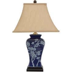 Inspired by classic Japanese design, this beautiful porcelain lamp features a bold style and rich blue glaze. Branches laden with cherry blossoms rise from the base of the lamp, the pale blue design s