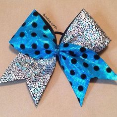 """This turquoise hologram fabric #cheerbow with black velvet polka dots and silver/black hologram fabric is made on 3"""" black grosgrain ribbon. It is secured in the center with 3/8"""" turquoise glitter ribbon.  All bows come with a pony tail holder. If you would like an alligator clip or barrette instead, please specify in order details."""