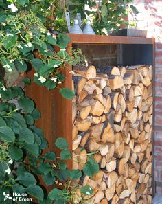 Corten steel storage for firewood, with the climbing Hydrangea on foreground