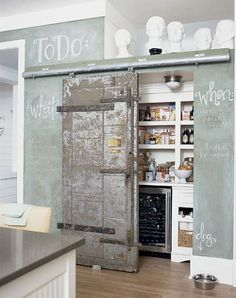 """A green chalkboard wall and sliding interior barn door gives this kitchen a loft-like feeling. The wine refrigerator is easily accessed when entertaining."""