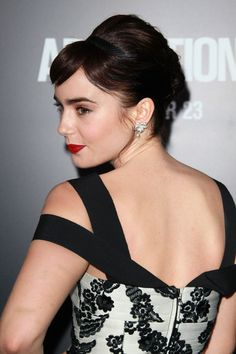 Lily Collins Bobby Pinned Updo - To duplicate Lily Collins' look, begin by sectioning out bangs, then backcomb the hair, especially through the crown. Next, throw on a slim headband and smooth tresses back to the nape of the neck. Twist hair vertically to create a low French twist and secure by inserting bobby pins horizontally into the twist, next to the scalp. To finish the look, sweep bangs across the forehead and mist with hairspray.