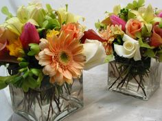 This is a cube vase floral arrangement that features gerbera daisies, roses and lilies in a pink, white and green color scheme.  See our entire selection at www.starflor.com.  To purchase any of our floral selections, as gifts or décor, please call us at 800.520.8999 or visit our e-commerce portal at www.Starbrightnyc.com. This composition of flowers is generally available for same day delivery in New York City (NYC). SQ115