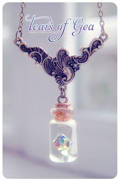 Un collar de botella de cristal pequeña hecha a mano con un diamante de swarovski flotante dentro. El líquido está teñido de resina de epoxy.