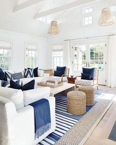 White and blue cottage living room features white slipcovered sofas adorned with blue pillows and blue fringe throw blankets facing a blond wood waterfall cocktail table placed atop a blue striped rug layered atop a gray bound sisal rug. Cottage Living Rooms, Coastal Living Rooms, Home Living Room, Living Room Designs, Blue Living Rooms, Navy And White Living Room, Coastal Rugs, Blue Rooms, Coastal Homes