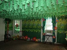 Jungle safari VBS. String wire across ceiling in a zigzag using cup hooks. Cut green plastic tablecloths and hang over wires to create vines in the sky. For curtains use green plastic tablecloths, green grass skirts from dollar tree, paper leaves and flowers. Attach all with staples.