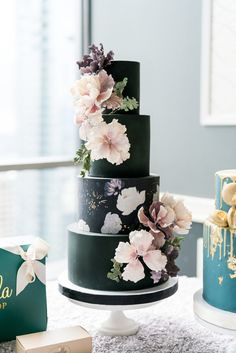 Onyx four-tiered wedding cake featuring a floral pattern and handmade sugar flowers, created by Vanilla Bake Shop.