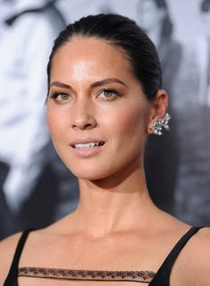 Olivia Munn looks elegant and refined with diamond earrings, slicked-back hair and minimal makeup that boasts soft pink lips.